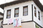 White washed house with black window frames with washing hanging by the windows to dry. Berat upper citadel old walled city. Albania, Balkan, Europe.