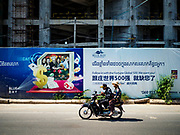 """13 FEBRUARY 2019 - SIHANOUKVILLE, CAMBODIA: Cambodians on a motorcycle pass Blue Bay resort and casino, a new resort being built by Chinese investors in Sihanoukville. There are about 80 Chinese casinos and resort hotels open in Sihanoukville and dozens more under construction. The casinos are changing the city, once a sleepy port on Southeast Asia's """"backpacker trail"""" into a booming city. The change is coming with a cost though. Many Cambodian residents of Sihanoukville  have lost their homes to make way for the casinos and the jobs are going to Chinese workers, brought in to build casinos and work in the casinos.      PHOTO BY JACK KURTZ"""