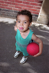 Nursery school boy standing in playground holding bouncy ball and sticking tongue out,