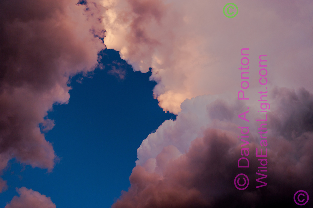 Sunset light creates multiple colors in storm clouds viewed from directly underneath, © David A. Ponton