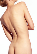Rear view of nude woman's flawless body with white background