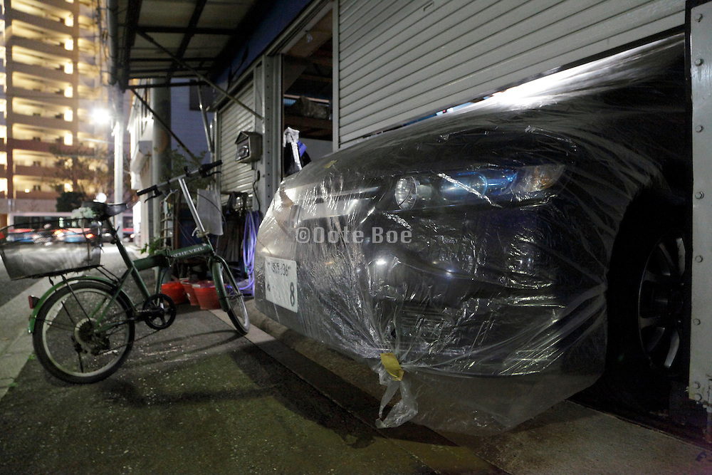 covered with plastic front of car sticking out under the garage door