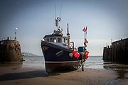 Opportunity FE 6 a Folkestone registered Fishing boats sit on the sand in a dry harbour entrance  due to the tide being out, waiting for the tide to come back in. Folkestone Harbour, Kent, United Kingdom.