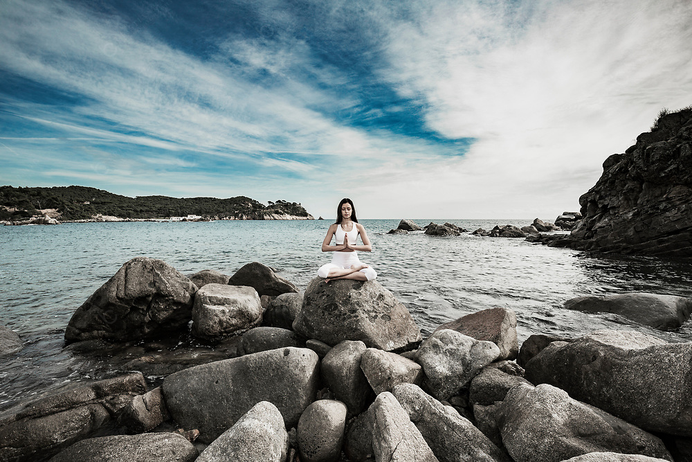 Young woman doing yoga at the sea