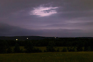 Town of Wallkill, New York -  Lightning streaks across the sky as fireflies shine in a field as a thunderstorm approaches in the Town of Wallkill, New York,  on June 25, 2014.