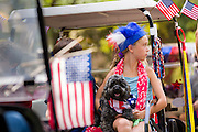 A young girl wearing patriotic costume holds her dog during the I'On neighborhood Independence Day parade July 4, 2015 in Mt Pleasant, South Carolina.