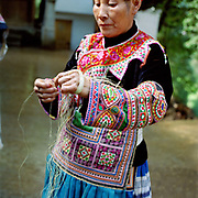 "A Red-Thread Miao ethnic minority woman, wearing her colourful appliqued traditional costume, splices ramie, Yi Xin village, Guizhou province, China. Ramie is one of the oldest fibre crops, having been used for at least six thousand years, and is principally used for fabric production. It is a bast fibre and the part used is the bark of the vegetative stalks. Almost 35% of Guizhou's population is made up of over 18 different ethnic minorities including the Miao. Each Miao group became isolated in these mountainous regions, hence the present day diversity in their culture, costume and dialects. According to a popular saying, ""if you meet 100 Miaos, you will see 100 costumes."""