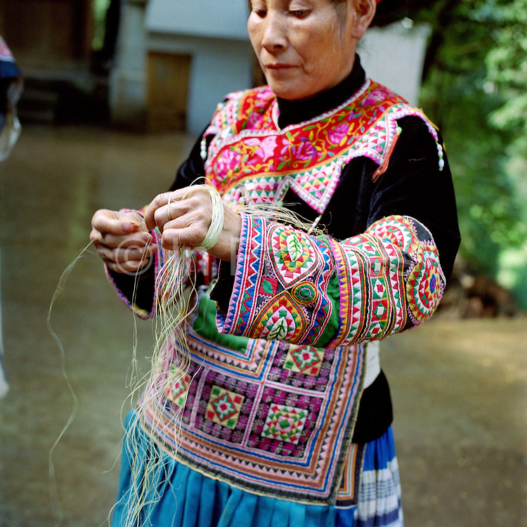 """A Red-Thread Miao ethnic minority woman, wearing her colourful appliqued traditional costume, splices ramie, Yi Xin village, Guizhou province, China. Ramie is one of the oldest fibre crops, having been used for at least six thousand years, and is principally used for fabric production. It is a bast fibre and the part used is the bark of the vegetative stalks. Almost 35% of Guizhou's population is made up of over 18 different ethnic minorities including the Miao. Each Miao group became isolated in these mountainous regions, hence the present day diversity in their culture, costume and dialects. According to a popular saying, """"if you meet 100 Miaos, you will see 100 costumes."""""""
