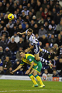 WBA's Gareth McAuley wins a header from Steven Whittaker of Norwich.  Barclays Premier league, West Bromwich Albion v Norwich city at the Hawthorns in West Bromwich, England on Sat 7th Dec 2013. pic by Andrew Orchard, Andrew Orchard sports photography.