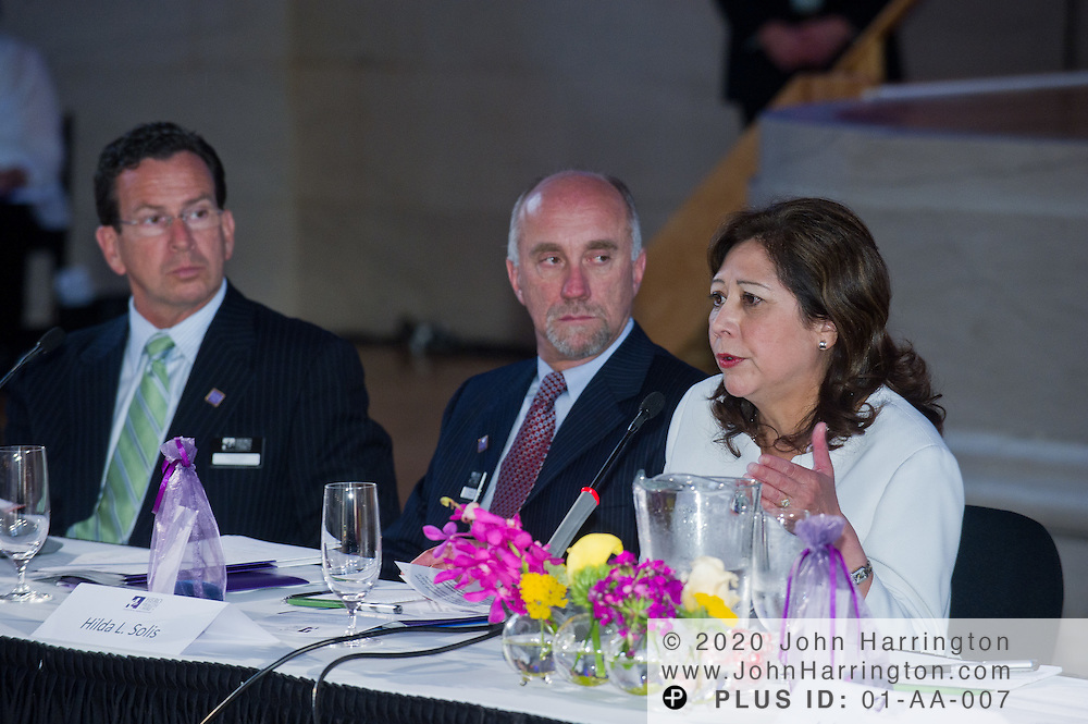 The Honorable Hilda L. Solis, U.S. Secretary of Labor, speaks while Rene Lerer (center), M.D., chairman and CEO of Magellan Health Services and Dannel Malloy (left), Gov. of Connecticut , look on during the Hero Health Hire Initiative Summit at the Andrew W. Mellon Auditorium in Washington, DC on June 22nd, 2011.