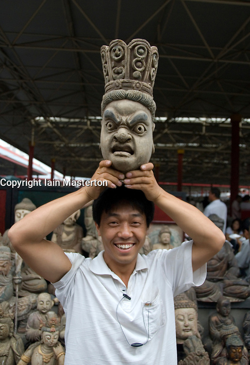 Man displaying a wooden bust at traditional antique market at Panjiayuan in Beijing China