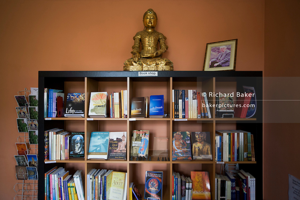 Bookshelves and Buddha at the Rivendell Buddhist Retreat Centre, East Sussex, England.