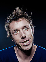 studio portrait on black background of a funny expressive caucasian man grimacing toothy smile