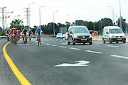 A group of cyclists ride on the edge of a highway