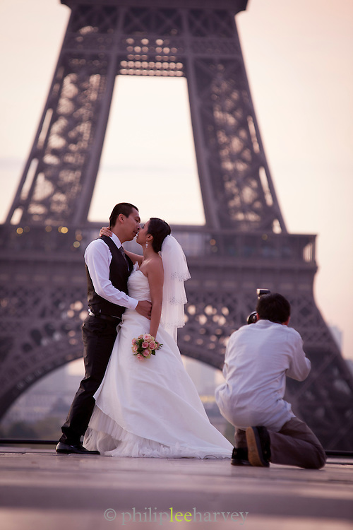 A newly married couple have their photographs taken at the Trocadero before the Eiffel Tower in Paris, France