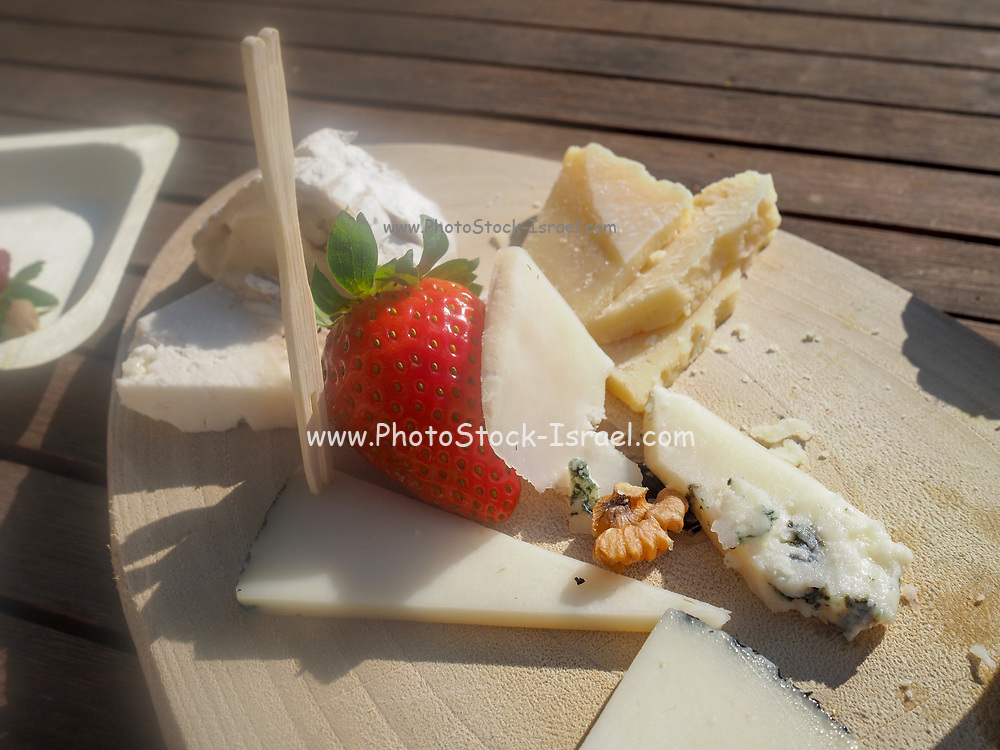Assortment of cheeses decorated with a perfect strawberry on a wooden platter