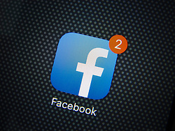 Facebook social media app logo on screen of iPhone 6 Plus smart phone