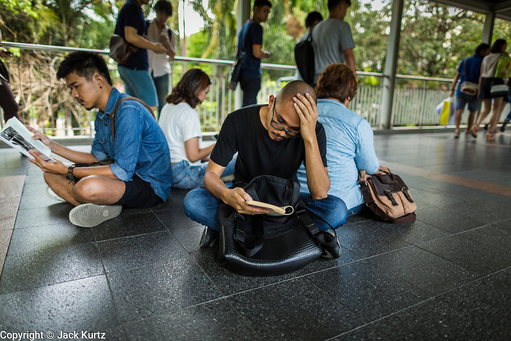 """31 MAY 2014 - BANGKOK, THAILAND:  People sit in the Skywalk between the BTS Skytrain Siam and Chit Lom stations to silently read George Orwell's """"1984"""" and other books about civil disobedience and nonviolent protest. The protests are based on the """"Standing Man"""" protests that started in Turkey last summer. Authorities made no effort to stop the protest or interfere with the people who were reading. Bangkok was mostly quiet Saturday. There were only a few isolated protests against the coup and military government.   PHOTO BY JACK KURTZ"""