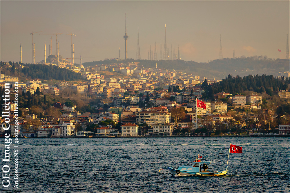A small pilot boat flying the Turkish flag travels along the Asian side of the Bosporus, which lined with predominantly upper-class residences, mosques, and communications towers, all in contrast to the vast wealth of Istanbul's elite on the European side of the waterway.