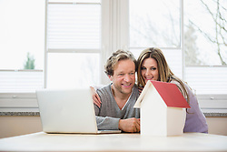 Couple with architectural model and laptop