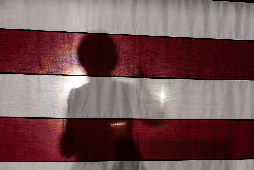 Long Island City, NY – 8 March 2019. Massachusetts Senator and Democratic Presidential candidate Elizabeth Warren drew an enthusiastic crowd at an organizing rally for her 2020 presidential campaign in Long Island City.Warren's figure casts a shadow as seen from behind the American flag behind the stage.