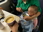 A woman feeds her grand son with instant noodles. Life in the seating wagons in the train from Hong Kong to Urumqi, Xinjiang.