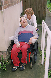 Carer pushing man with Cerebral Palsy in wheelchair up slope in park,