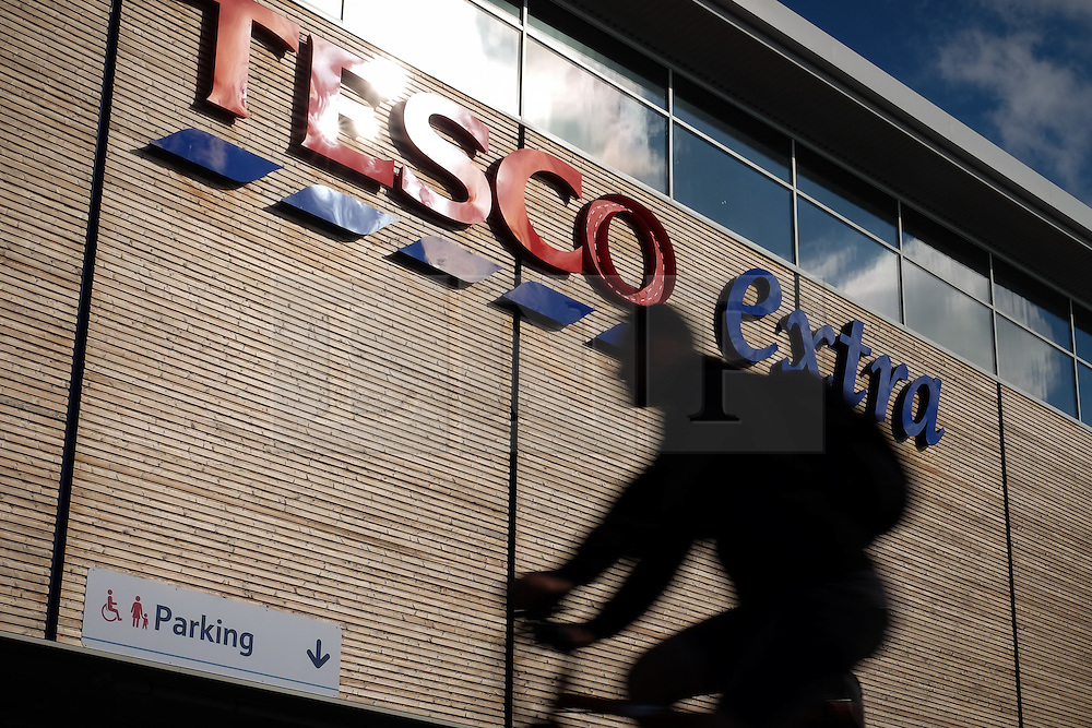 © Licensed to London News Pictures. 05/10/2016. Portsmouth, Hampshire, UK.  A man cycling past a Tesco Extra in Portsmouth this morning. Tesco PLC, Britain's largest supermarket chain has announced that like-for-like sales had grown in the first half of its financial year. The results come following increased competition in the market from budget supermarkets such as Aldi & Lidl. Photo credit: Rob Arnold/LNP