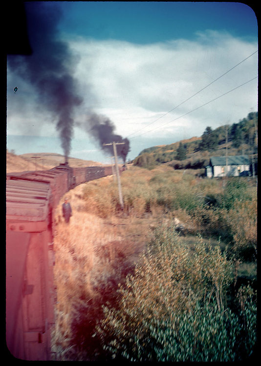 Long freight with mid-train helper engine, location uncertain.  View is from caboose.<br /> RGS ?    Taken by Rasmussen, Forest