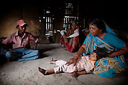 Meenakshi, 7, a young girl suffering from a severe neurological disorder, is being cared by her mother (right) while sitting inside their home in the impoverished Oriya Basti colony, Bhopal, Madhya Pradesh, India, near the abandoned Union Carbide (now DOW Chemical) industrial complex.