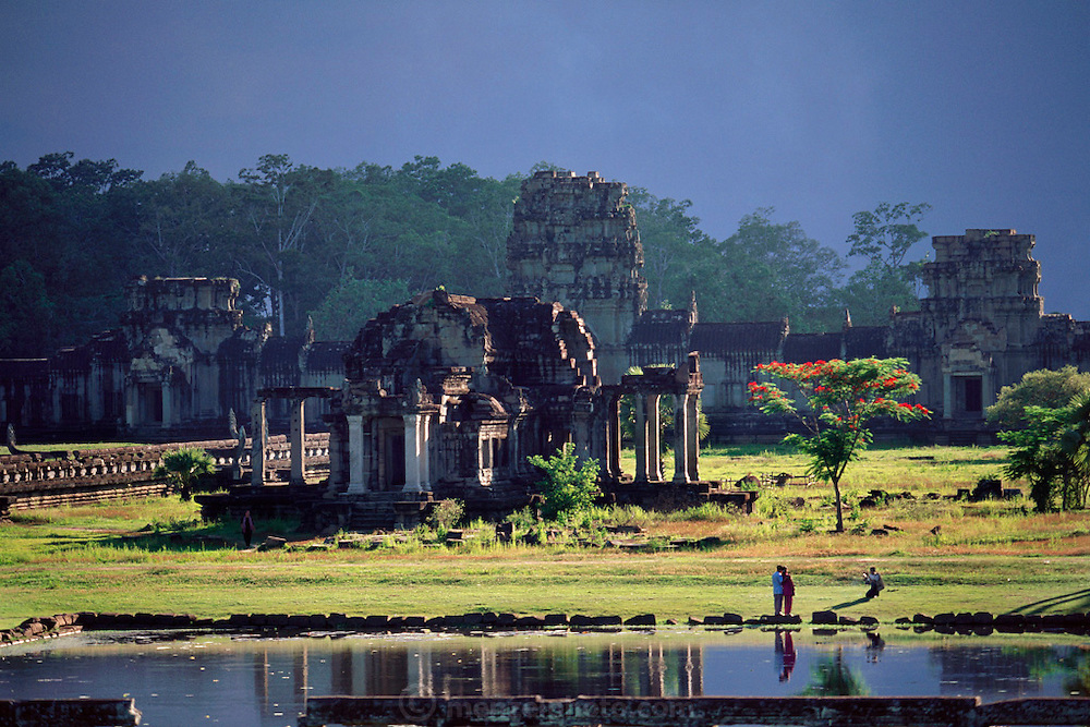Ruins at Angkor Wat, Cambodia. The temples at Angkor are spread out over some 40 miles around the village of Siem Reap, about 192 miles from the Cambodian capital, Phnom Penh. They were built between the eighth and 13th centuries and range from single towers made of bricks to vast stone temple complexes. Regarded as the supreme masterpiece of Khmer architecture, it is a huge pyramid temple built by Suryavarman II between 1113 and 1150. It is surrounded by a moat 570 feet wide and about four miles long. The bas-relief carvings are of the highest quality and the most beautifully executed in Angkor..
