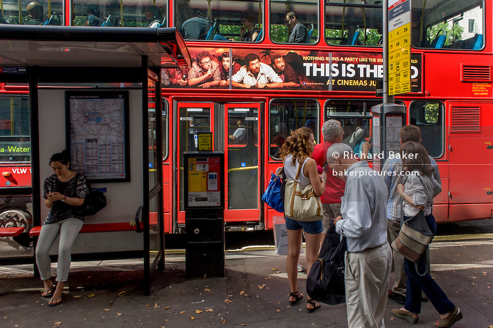London commuters at a bus stop below a red London double-decker bus with a Hollywood blockbuster film banner.