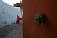 Detail of an old door ring with a monk walking in background, Tango Monastery, Bhutan, Asia