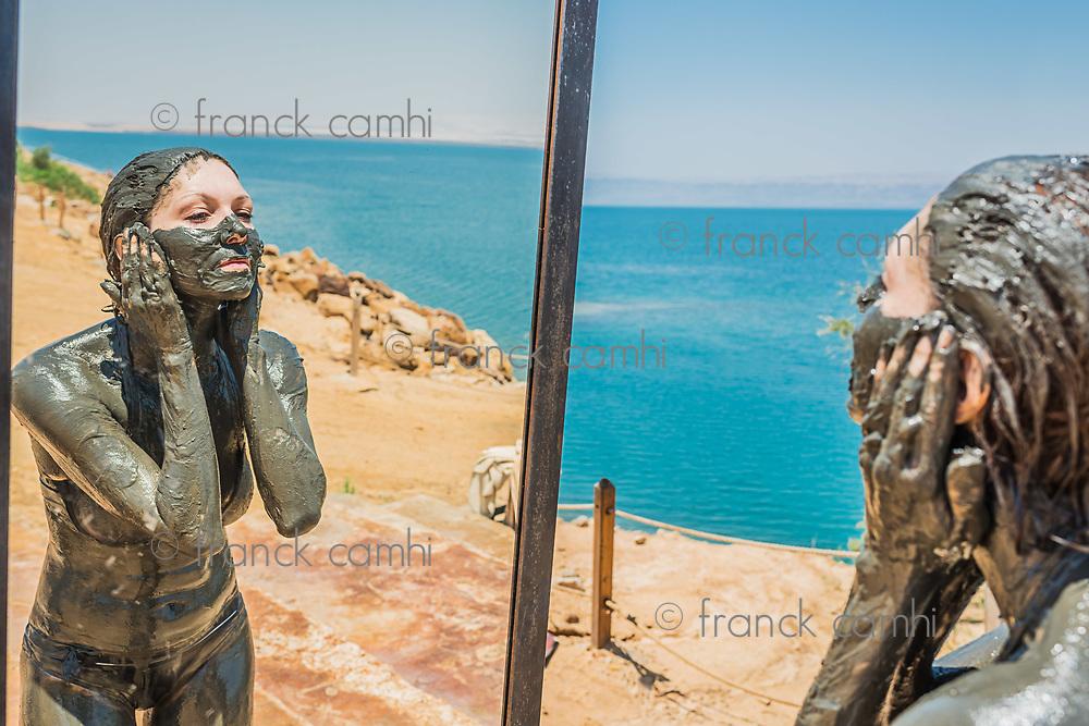 one  woman applying Dead Sea mud body care treatment in Jordan