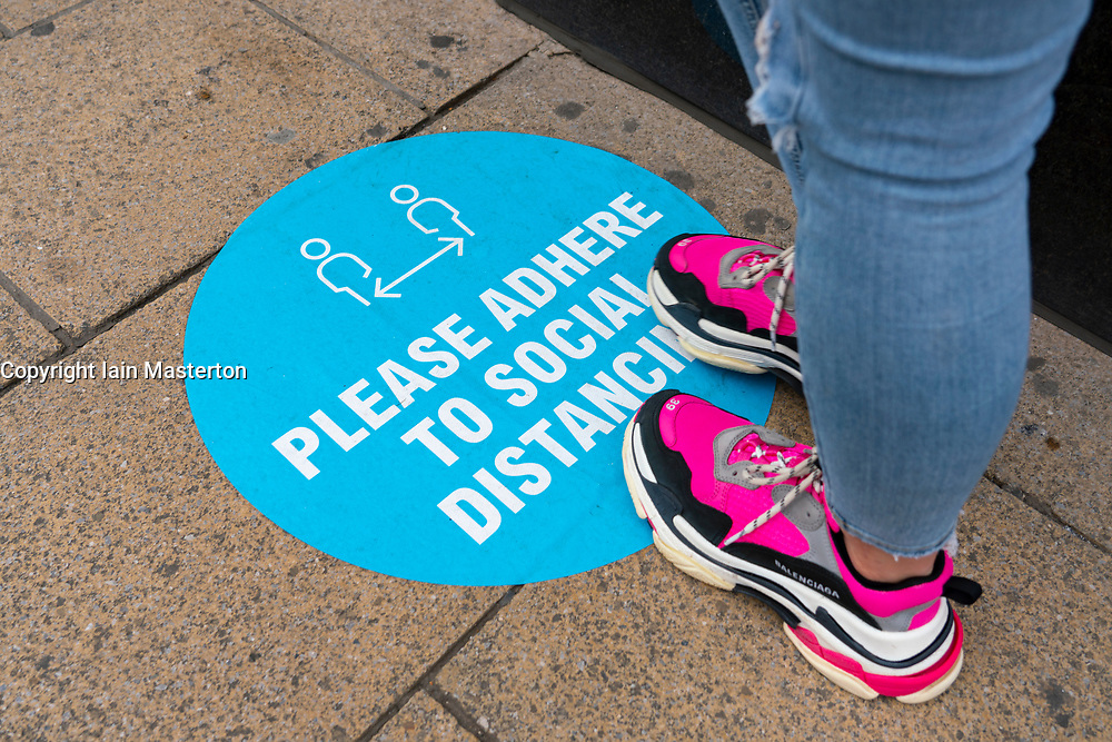 Edinburgh, Scotland, UK. 2 July, 2020. Good weather brought many shoppers out onto Princes Street in Edinburgh. Still busy with people queuing around the block was Primark. Pictured; Social distancing sign on pavement.  Iain Masterton/Alamy Live News