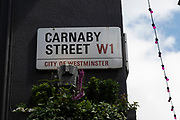 Street sign for the famous Carnaby Street W1 on 26th May 2021 in London, United Kingdom. Carnaby Street is a pedestrianised shopping street in Soho in the City of Westminster. Infamous as a street where people would come to parade their fashions in the 1960s, it is home to fashion and lifestyle retailers, including many independent fashion boutiques.