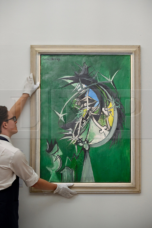 """© Licensed to London News Pictures. 17/07/2019. LONDON, UK. A technician presents """"Thorn Head"""", 1947, by Graham Sutherland at the preview of """"Brave New Visions: The Émigrés who transformed the British Art World"""", a new exhibition at Sotheby's gallery in New Bond Street which runs 17 July to 9 August 2019.  The show is also part of """"Insiders / Outsiders"""", a nationwide, year long festival celebrating refugees from Nazi Europe and their contribution to British culture.  Photo credit: Stephen Chung/LNP"""
