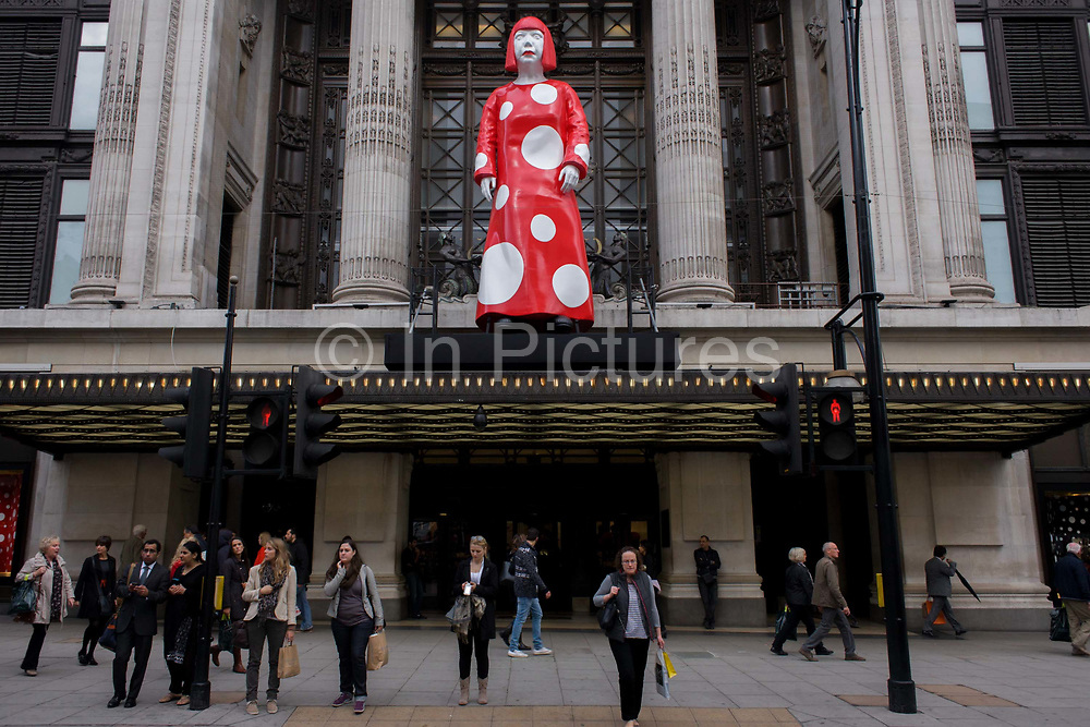 Giant model in red and white spotted display of artist Yakoi Kusama whose collaboration between Louis Vuitton and Selfridges whose red campaign theme accompanies a life size model of the artist in the department store windows and Oxford Street entrance. Yayoi Kusama (1929) is a Japanese artist and writer. Throughout her career she has worked in a wide variety of media, including painting, collage, sculpture, performance art and environmental installations, most of which exhibit her thematic interest in psychedelic colors, repetition and pattern.