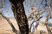 02 APRIL 2006 - THREE POINTS, AZ: JERRY GREENE, a Minuteman volunteer from Minnetonka, MN, scans the desert from a tree stand for signs of illegal immigrants during the Minuteman Project action on Elkhorn Ranch Rd. between Three Points, AZ, and Sasabe, AZ, about 60 miles south of Tucson, AZ, April, 2, 2006. Volunteers from the Minuteman Project have set up lines of observation posts on remote county roads in the desert southwest of Tucson to monitor the area for illegal immigrant traffic. On Saturday night, the first night of the action, Minuteman volunteers spotted more than 50 illegal immigrants and claim their tips to the US Border Patrol led to the apprehension of at least 16 of those immigrants.  Photo by Jack Kurtz