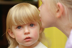 Closeup portrait of young girl with blond hair looking serious,