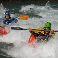 Kayakers David Manning and Mikkel St. Jean-Duncan play in waves on the Kananaskis River in the Canadian Rockies near Calgary, Alberta.
