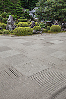 Tofukuji Fumo-in is a Zen garden in Kaisan-do, sub-temples at Tofuku-ji. The dry landscape karesansui garden here is composed of gravel raked into rectangles of sand arranged in a checkerboard fashion. At the end of the dry garden there is a small island with rocks and trees representing a turtle and a crane which are symbols of longevity. The stone path that cuts through the garden in front of the main hall results in one of the most unique gardens in Kyoto.  On the east side of the path the lush pond garden has a stone bridge, shrubs and a hill.