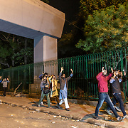 Students from Jamia University forced to exit the campus area with their hands raised above their heads.