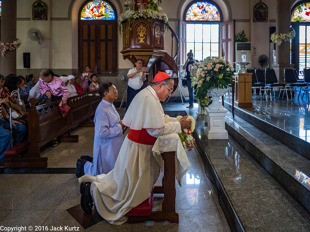 18 SEPTEMBER 2016 - BANGKOK, THAILAND: FRANCIS XAVIER KRIENGSAK, the Archbishop of Bangkok, prays in the sanctuary of Santa Cruz Church before leading the church's 100th anniversary mass. Santa Cruz Church before leading the church's 100th anniversary mass. Santa Cruz Church was establised in 1769 to serve Portuguese soldiers in the employ of King Taksin, who reestablished the Siamese (Thai) empire after the Burmese sacked the ancient Siamese capital of Ayutthaya. The church was one of the first Catholic churches in Bangkok and is one of the most historic Catholic churches in Thailand. The first sanctuary was a simple wood and thatch structure and burned down in the 1800s. The church is in its third sanctuary and was designed in a Renaissance / Neo-Classical style. It was consecrated in September, 1916. The church, located on the Chao Phraya River, serves as a landmark for central Bangkok.       PHOTO BY JACK KURTZ