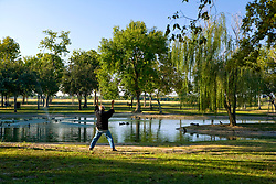 Older man practicing tai chi beside the pond at Storey Park in Houston, Texas
