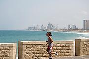 Israel, Tel Aviv-Jaffa, man running  on the beach front promenade Tel Aviv's beach front in the background