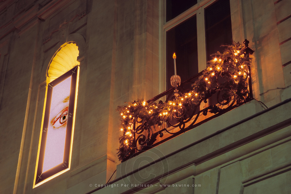 The exterior with neon signs of an eye and Christmas decorations, crystal candle candelabra. At The Baccarat museum, shop, restaurant at the Hotel de Noailles in Paris. Designed by Philippe Starck.