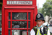 """London, United Kingdom, July 24, 2021: A Police officer stands beside a red box telephone booth near Trafalgar during an """"anti-Lockdown"""" demonstration in central London, on Saturday, July 24, 2021. (VX Photo/ Vudi Xhymshiti)"""