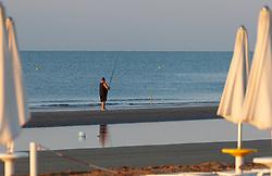 THEMENBILD - ein Fischer am Sandstrand in der Sonne, aufgenommen am 16. Juni 2018, Lignano Sabbiadoro, Österreich // a fisherman on a sandy beach in the sun on 2018/06/16, Lignano Sabbiadoro, Austria. EXPA Pictures © 2018, PhotoCredit: EXPA/ Stefanie Oberhauser
