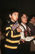 A young Korean boy waves an American flag during an immigration naturalization ceremony November 12, 1996 in Washington, DC.